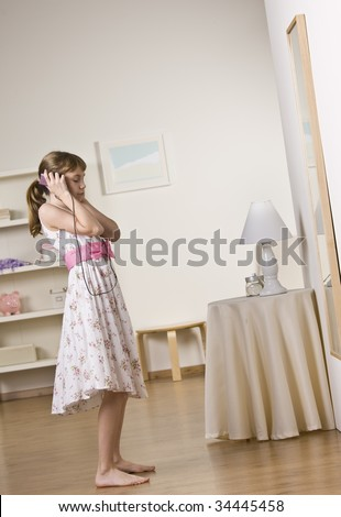 A young girl listening to music with headphones.  Vertically framed shot. - stock photo