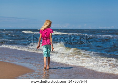 A young girl looking for beautiful shells