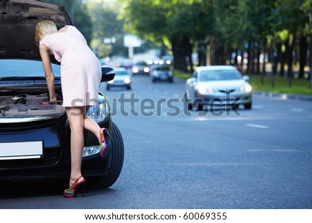 A young girl looks into the open hood - stock photo
