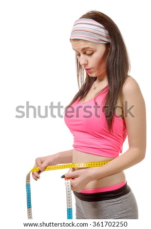 a young girl making measure around her waist with measuring tape - stock photo