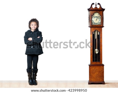 A young girl next to a grandfather clock indicates that growth takes time. - stock photo