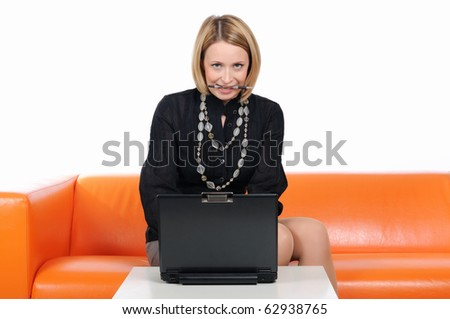 A young girl on an orange sofa, working at a laptop - stock photo