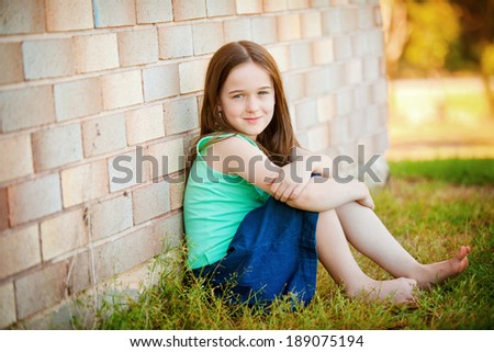 A young girl outdoors leaning up against a brick wall.   Plenty of negative space on the brick wall.  She is happy and relaxed in a jeans skirt and blue top