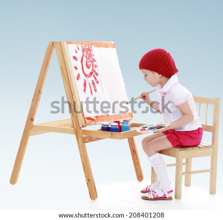 A young girl paints the artist at the easel.kindergarten, the concept of childhood and joy, teens - stock photo