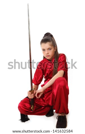 A young girl performs a complex  of style Shaolin with a sword - stock photo