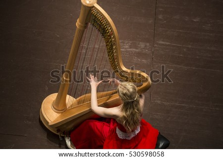A young girl playing the harp during concert at musical theater