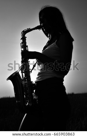 A young girl plays the saxophone on the nature of black and white photos