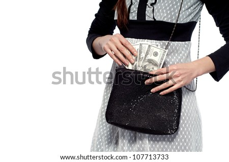 A young girl pulls dollars out of the bag. On a white background.