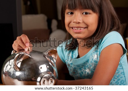 a young girl puts some money into her piggybank - stock photo