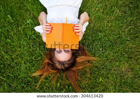 A young girl reading a book lying on a green lawn in the park. Summer day. - stock photo