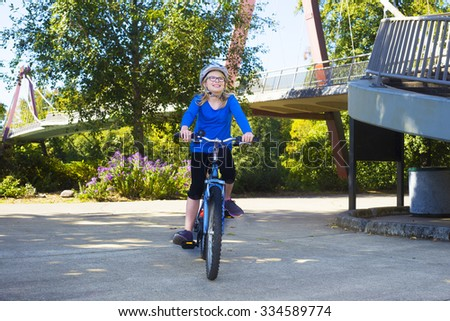 A young girl rides along the bike path at Alton Baker Park by the DeFazio bike bridge in Eugene Oregon - stock photo