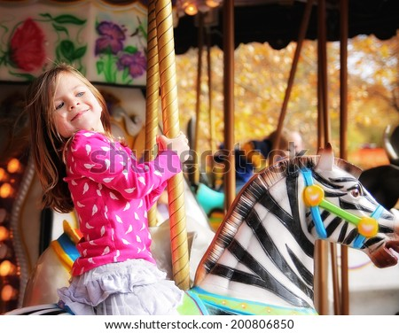 a young girl riding on a merry go round at the zoo - stock photo