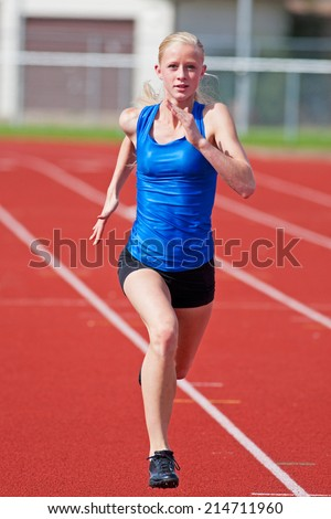 A young girl running on a track towards the camera. - stock photo