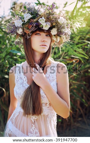a young girl. shore of a mountain river. ethnic motifs. a wreath of wild herbs. handmade. professional makeup. long brown hair. Fresh air. Spring concept. spring came. - stock photo