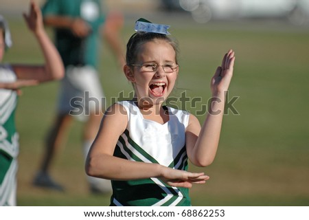 A young girl shows enthusiasm while cheering her team on - stock photo