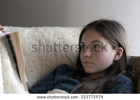 A young, girl sits on the sofa while the outside sunlight shines softly through the window onto her and the book. She is reading a very serious and intent book. Plain background and horizontal format. - stock photo