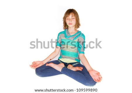 A young girl sitting crosslegged meditating.