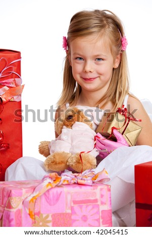 a young girl sitting in the middle of her presents - stock photo