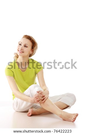 A young girl sitting on the floor - stock photo