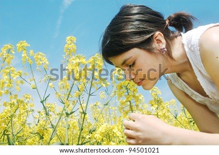 A young girl smelling a canola spring flower. - stock photo