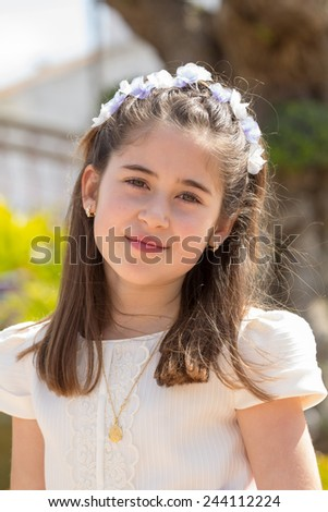 A young girl smiling and celebrating her First Holy Communion - stock photo