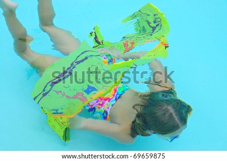 A Young girl swimming through a hoop under water. - stock photo
