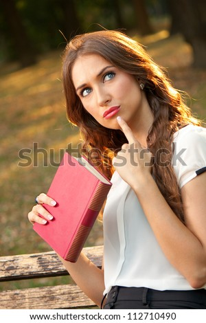 A young girl thinks in the park - stock photo