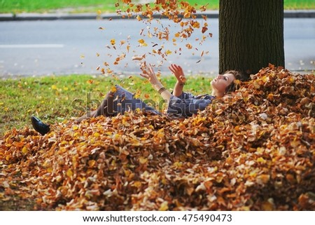 a Young girl throwing autumn leaves in the air, lying on the ground in a big pile of fallen leaves.