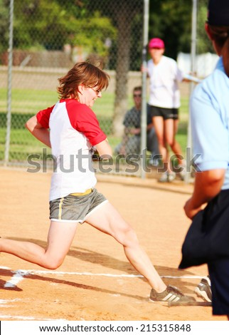 a young girl touching home plate in a softball game - stock photo