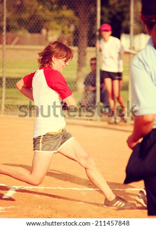 a young girl touching home plate in a softball game toned with a retro vintage instagram filter - stock photo
