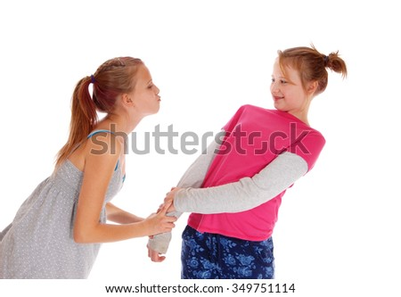 A young girl tried to give her sister a kiss but she dose not like it,isolated for white background. - stock photo
