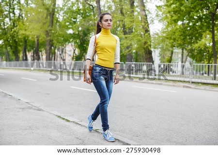 a young girl walks along the road - stock photo