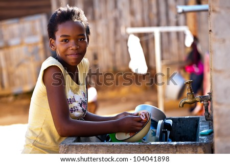 A young girl washing the dishes outside by the sink. - stock photo