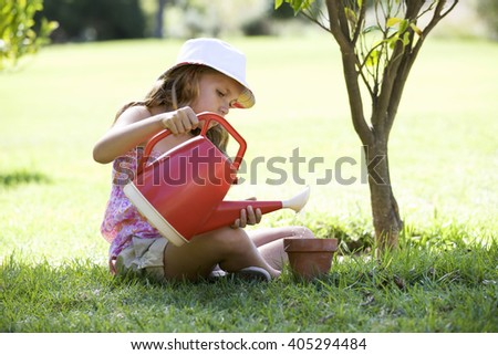A young girl watering seeds in a plant pot - stock photo
