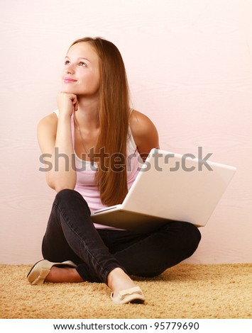 A young girl with a laptop sitting on the floor next to the wall