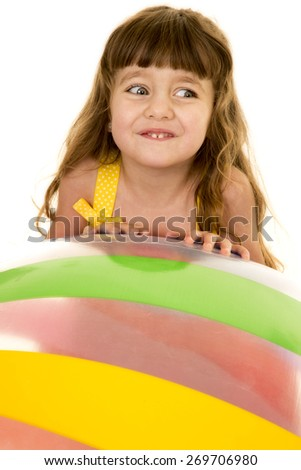 A young girl with a smile on her face, looking over to the side, laying on a beach ball - stock photo
