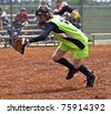 A young girl with ball in hand racing to make an out in a softball game. - stock photo