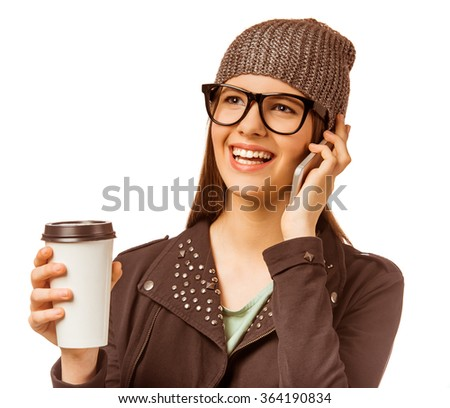 A young girl with big glasses, drinking coffee and talking on the phone isolated on a white background - stock photo