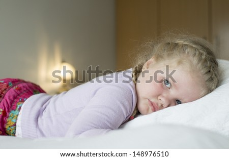 A young girl with braids on bed