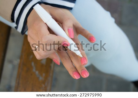 A young girl with bright pink manicure gets oil on the cuticles sitting on a bench on the street - stock photo