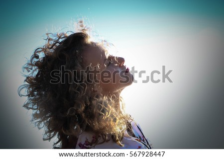 a young girl with curly hair in the sunlight