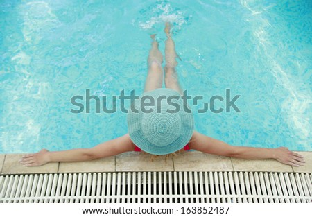 a  young girl with hat in water pool