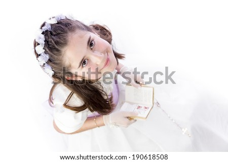 A young girl with rosary and prayer book celebrating her First Holy Communion - stock photo