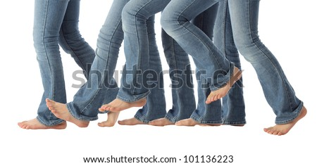 A young girls bare feet advance one step forward in jeans on white