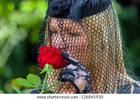 a young, grieving widow with a veil and rose. death and inheritance. - stock photo