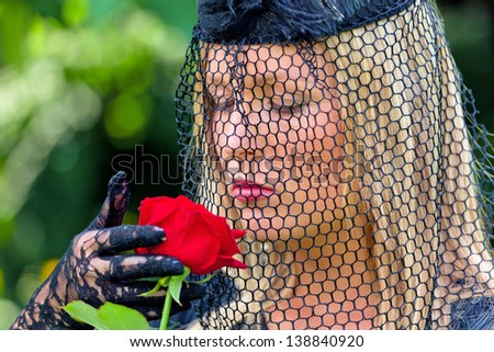 a young, grieving widow with veil and rose. death and inheritance. - stock photo