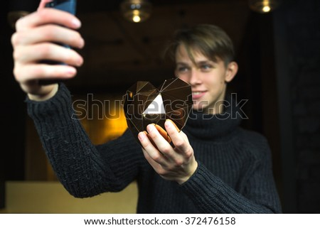 a young guy holding a heart. Golden heart. a young man makes a selfie with heart - stock photo