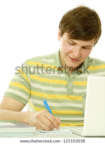 A young guy in front of a laptop studying, isolated on white - stock photo