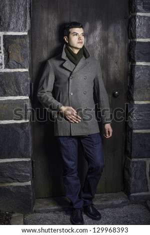 A young guy is standing by a door, waiting for you.
