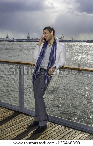 A young guy is standing on the dock, smiling and talking on the phone.